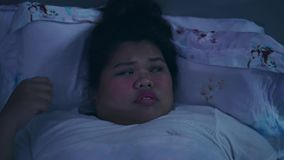 Frustrated overweight woman with insomnia. Frustrated overweight young woman suffering from insomnia, closing her head while lying on the bed at night. Shot in stock footage