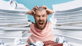 Frustrated overwhelmed executive working in the office and overloaded with paperwork. He is screaming and feeling depressed stock photography