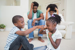 Frustrated parents watching their children fight. At home in the living room Stock Photography