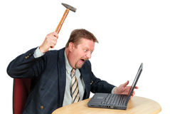 Frustrated PC user. Fustrated user or businessman in his office threatening to destroy his PC with a hammer out of sheer frustration for malfunctions, faulty or Stock Image