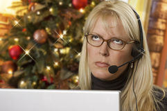Frustrated Phone Receptionist Using Laptop Wearing Headset Near Christmas Tree Stock Photo