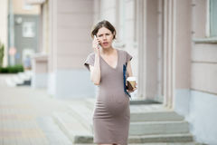 Frustrated pregnant business woman on phone Royalty Free Stock Photos