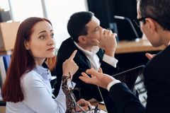 Frustrated red-haired woman points finger at adult man who turned to other way, at lawyer`s office. stock images