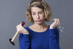 Frustrated 20s woman being bored at mechanics handiwork or DIY Stock Photos