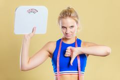 Sad woman with weight gain thumb down sign. Frustrated sad blonde girl holding scales, making thumb down gesture sign. Weight gain, time for slimming weightloss Royalty Free Stock Photos