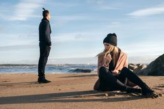 Frustrated sad girlfriend sit on sand think of relationship problems. Thoughtful couple after quarrel lost in thoughts, upset lovers on the coastline royalty free stock photography