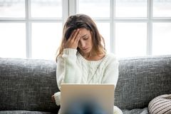 Frustrated woman worried about problem sitting on sofa with lapt Royalty Free Stock Photography