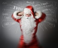 Frustrated Santa Claus and many wishes. Headache concept. Stock Image