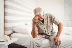 Frustrated senior man sitting on bed Stock Image