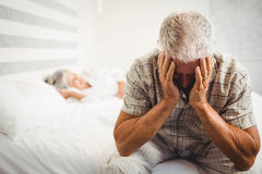 Frustrated senior man sitting on bed. Frustrated senior men sitting on bed in bedroom Royalty Free Stock Image