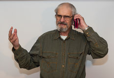 Frustrated senior man talking on the phone. Frustrated senior man talking on the phone Royalty Free Stock Photography