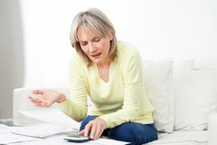 Frustrated senior woman. With paperwork and calculator at home Stock Photo