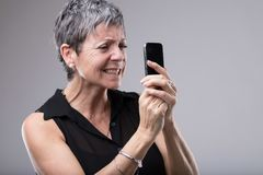 Frustrated woman gnashing her teeth. Frustrated senior woman gnashing her teeth as she grips her mobile phone tightly in her hands while reading text message stock photography