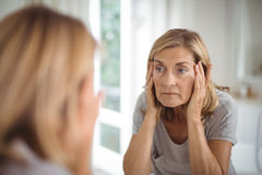 Frustrated senior woman looking at mirror. In bathroom Stock Photography