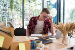 Frustrated startup small business owner working at workplace. st. Ressed freelance man seller check product order for delivery to customer. Online selling, e royalty free stock image