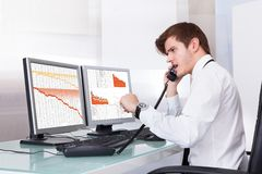 Frustrated Stock Broker Working At Office. Frustrated Young Stock Broker Using Telephone Sitting In Front Of Desktop Stock Photography