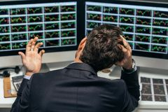 Frustrated stock trader. Rear view of frustrated stock trader looking at the financial graphs stock photography