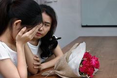 Frustrated stressed Asian woman comforting a sad depressed female friend. Break up or best relationship concept. Frustrated stressed Asian women comforting a Royalty Free Stock Photo