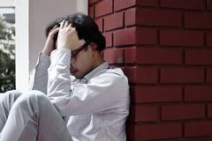 Frustrated stressed young Asian business man feeling disappointed or exhausted with job at outside office. Frustrated stressed young Asian business man feeling Stock Photo