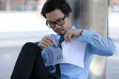 Frustrated stressed young Asian business man tearing up charts at outside office stock photos