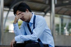 Frustrated stressed young Asian businessman touching head and feeling tired and exhausted with his job royalty free stock photography