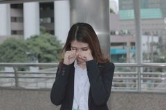 Frustrated stressed young Asian businesswoman crying closed face with her hands at outside office. Royalty Free Stock Images