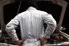 Frustrated stressed young mechanic man in white uniform feeling disappointed or exhausted with car in open hood at the repair gara stock photo