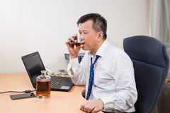 Frustrated and stressful Asian manager drinking hard liquor in o Stock Image