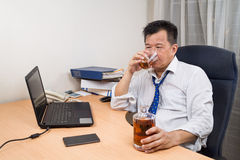 Frustrated and stressful Asian manager drinking hard liquor in o Royalty Free Stock Images