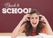 Frustrated student girl at table against red blackboard with back to school text Royalty Free Stock Photography