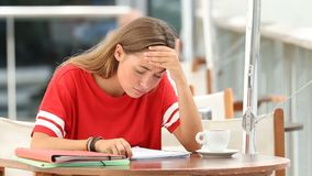 Frustrated student studying in a coffee shop. Frustrated student studying reading noted of a difficult lesson in a coffee shop stock video