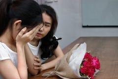 Frustrated subrayó a la mujer asiática que confortaba a un amigo femenino deprimido triste Rómpase para arriba o el mejor concept Foto de archivo libre de regalías