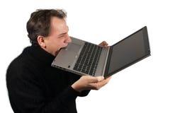 Frustrated subrayó mordeduras del hombre en ordenador portátil desesperadamente Foto de archivo