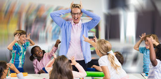 Composite image of frustrated teacher with naughty students royalty free stock photography