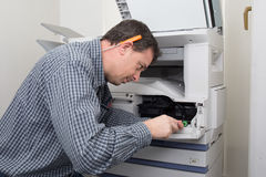 Frustrated technician man opening photocopy machine stock images