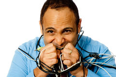 Frustrated With Technology. A businessman is tied up with cables and frustrated with technology. Isolated on white Royalty Free Stock Photos