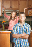 Frustrated teen stands with arms crossed as his mother throws he Stock Images