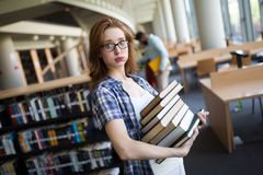 Frustrated teen student girl with books. Frustrated teen student girl with a lot of books Royalty Free Stock Photos