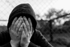 Frustrated teenage boy covering hes face in front of correctional institutes wired fence, conceptual image of juvenile delinquency. Shallow depth of field royalty free stock photography