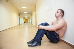 Frustrated teenage boy with naked torso sitting tucked her knees in the corridor Royalty Free Stock Images