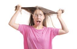 Frustrated teenage girl with braces pulling out her hair Stock Photo