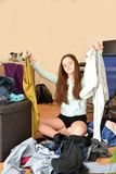 Frustrated teenage girl choosing her outfit. Nothing to wear. Teenage girl sits on the floor in the chaos of her clothes, looking frustrated stock images