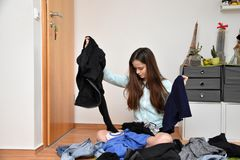 Frustrated teenage girl choosing her outfit stock images