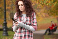 Frustrated Teenage Girl Making Mobile Phone Call. In Autumn Landscape Royalty Free Stock Photography