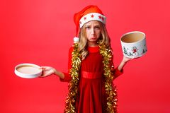Frustrated teenage girl in Santa hat and tinsel on neck, sadly holding empty box on red background royalty free stock photography