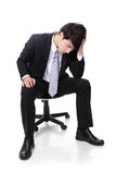 Frustrated and thinking business man sitting Royalty Free Stock Photography