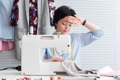 Frustrated tired seamstress touching her head, feeling absolutely exhausted because of overwork, working at tailor shop with elect. Rical industrial sewing stock photos
