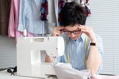 Frustrated tired seamstress touching her head, feeling absolutely exhausted because of overwork, working at tailor shop with elect. Rical industrial sewing stock image