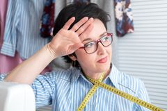 Frustrated tired seamstress touching her head, feeling absolutely exhausted because of overwork, working at tailor shop with elect. Rical industrial sewing stock photo