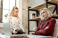 Frustrated unpleasant mother sitting with crossed hands. Insufferable gesture. Frustrated unpleasant mother sitting with crossed hands while offended daughter royalty free stock photo